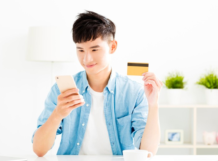 A young man with a smartphone in one hand and a credit card in the other.