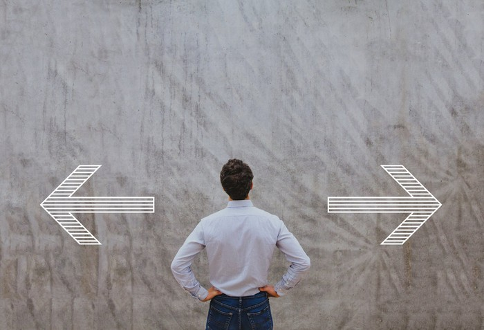 Man with hands on hips looking at arrows on a wall pointing left and right.