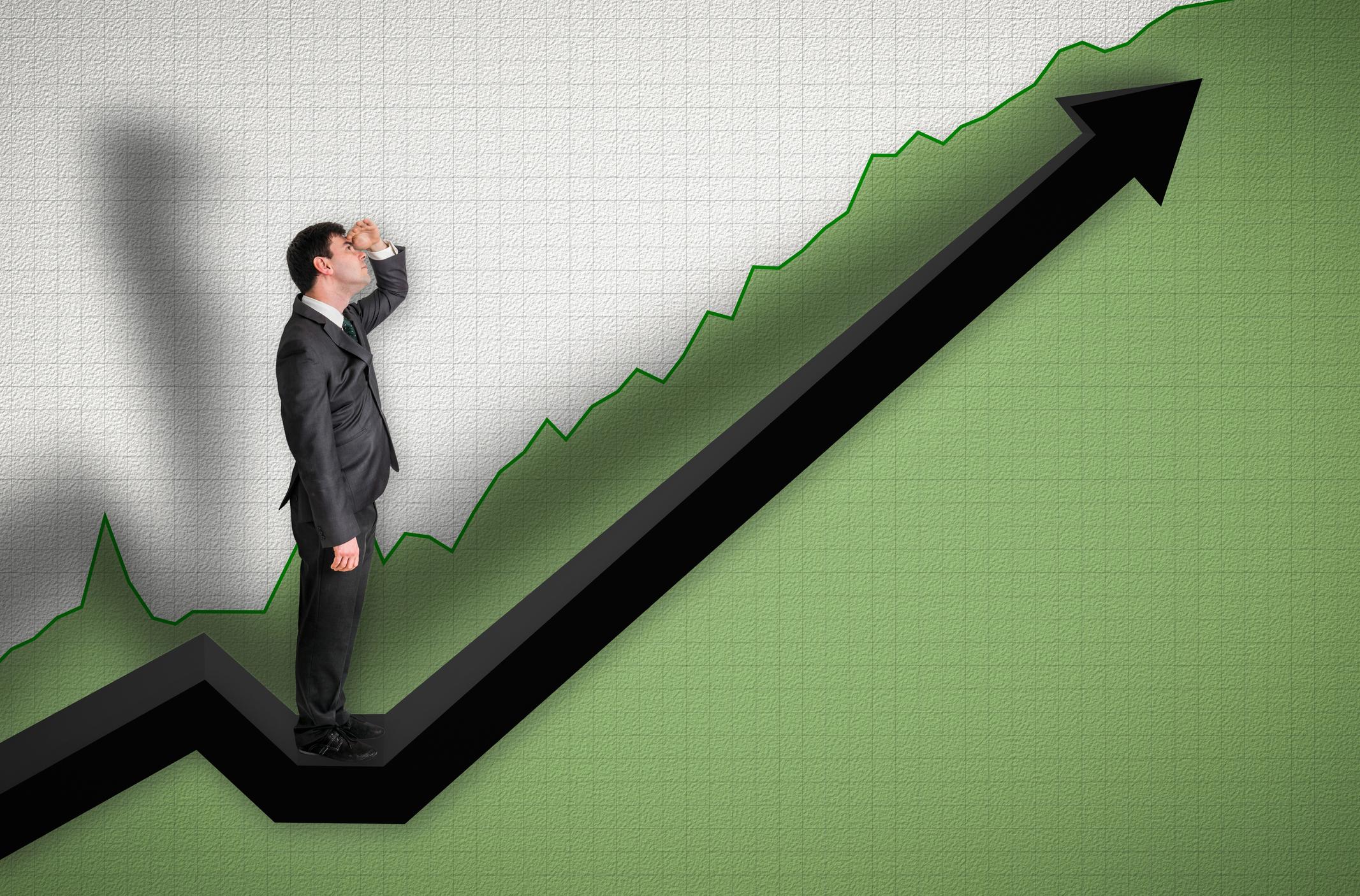 Businessman watching chart go up