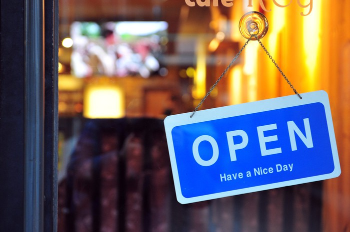 An open sign hangs on a small business's door.