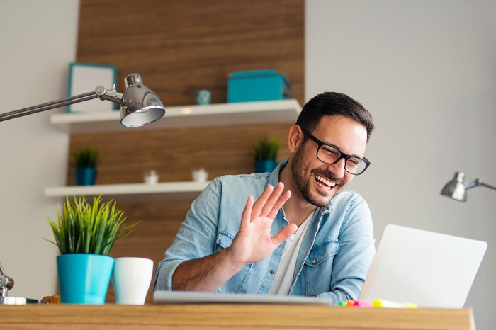 A smiling young man waving at the screen of a laptop computer