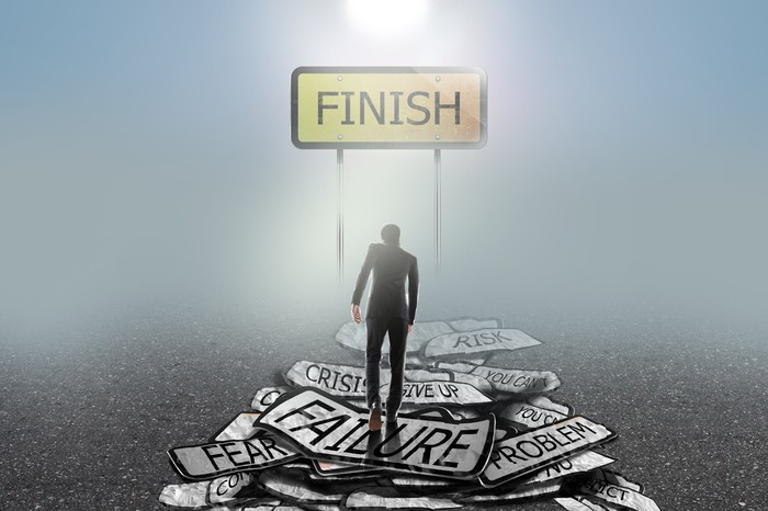 A man in a suit climbing a mountain of failure signs toward a finish line.