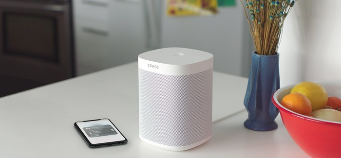 SONOS Airplay 2 smart speaker on a table next to a bowl of fruit and a smartphone