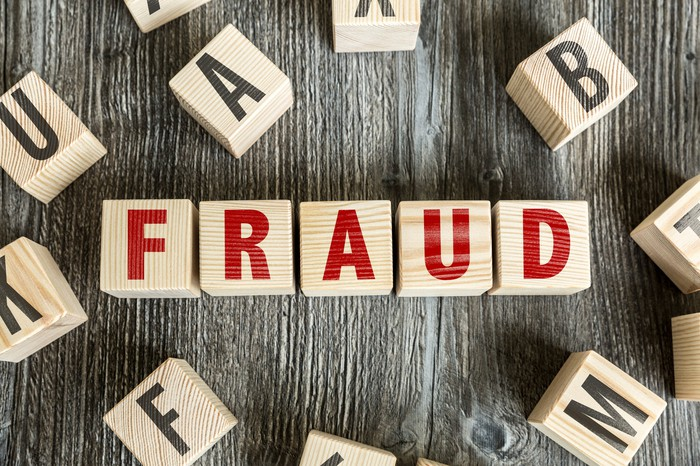 Red letters on wood blocks that spell out the word fraud.