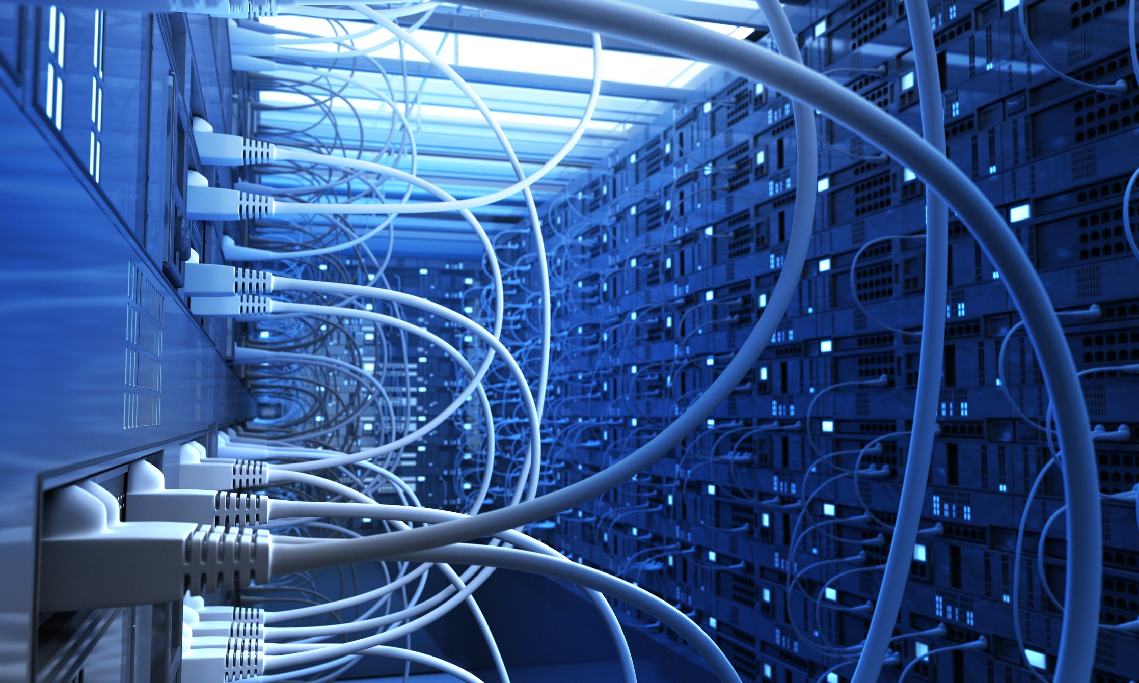 Photo of a data center cast in blue light with several power cords and cables connecting the stocks of routers and switches.
