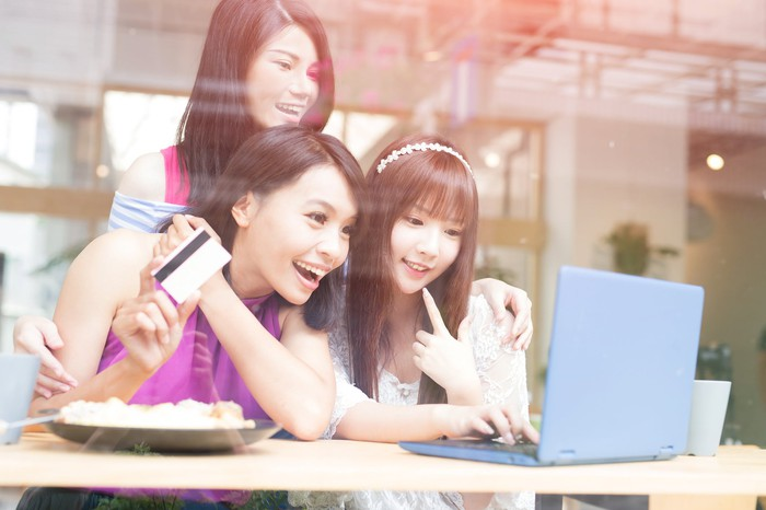 Three women looking at a laptop screen. One of them is holding a credit card.