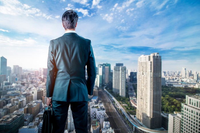 A man in a suit looming over a cityscape at daytime.