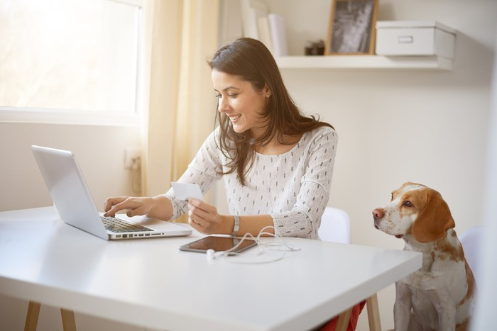 Woman at a desk working at a laptop while a dog looks on.