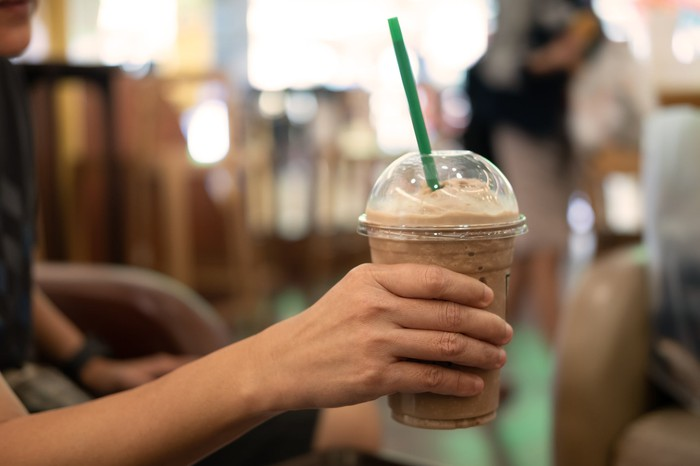 Woman holding a cup of store-bought iced coffee.