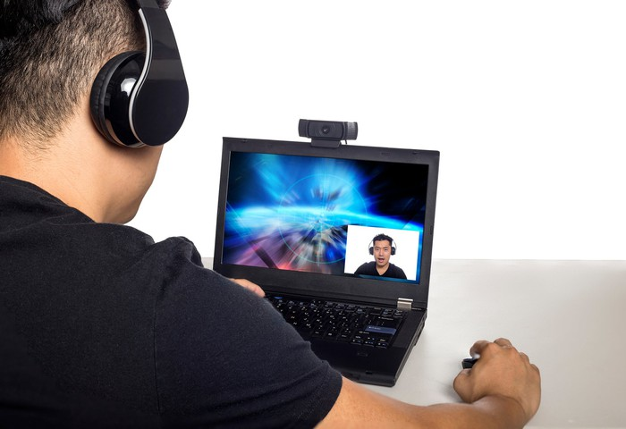 Back view of a man with headphones who is looking at a laptop.