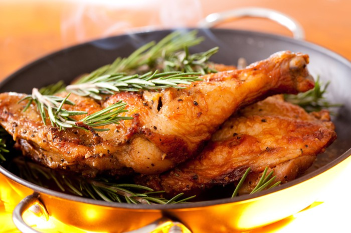 Roasted chicken in a pan, topped with rosemary.