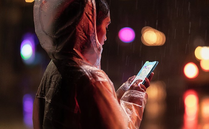 A woman holding an iPhone XR at night, in the rain