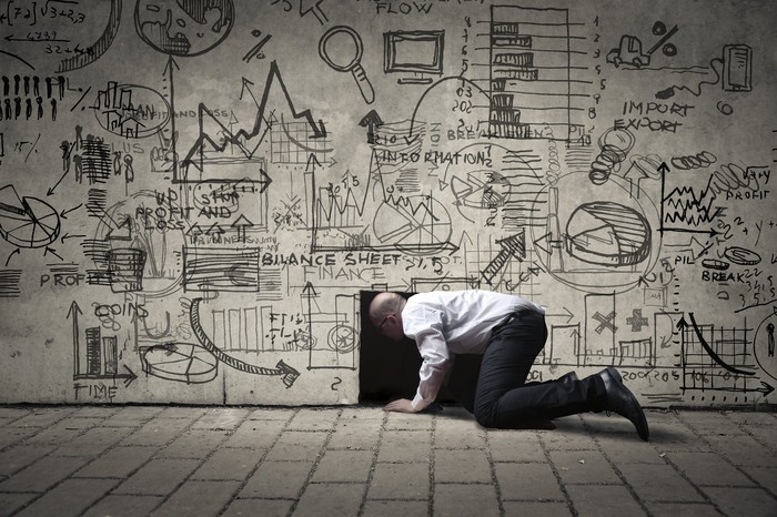 Man on knees looking through opening at bottom of a wall covered with business diagrams.