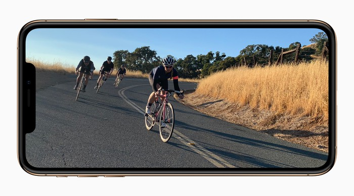 An Apple iPhone Xs with an image of four cyclists riding down a hill with tall grass on the sidelines.