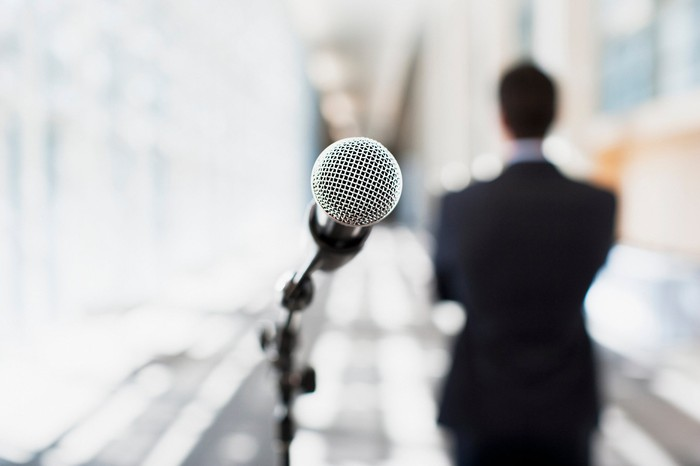 A microphone on a stand in the foreground with a person wearing a suit in the background.