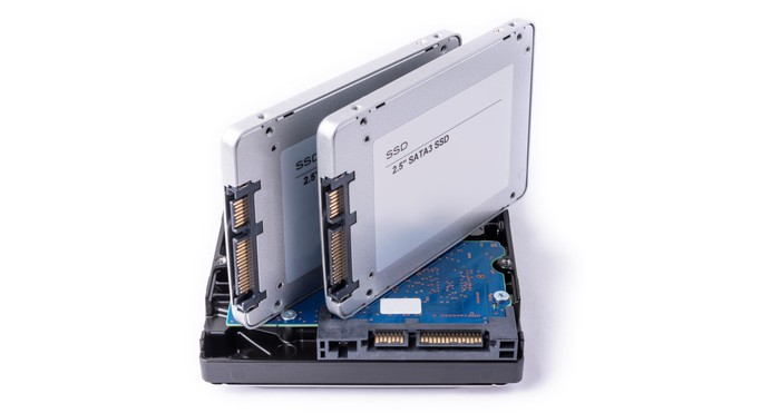 Two SSDs placed on top of a traditional HDD.