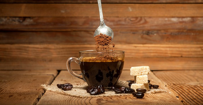 A spoon stirs coffee on a wooden countertop