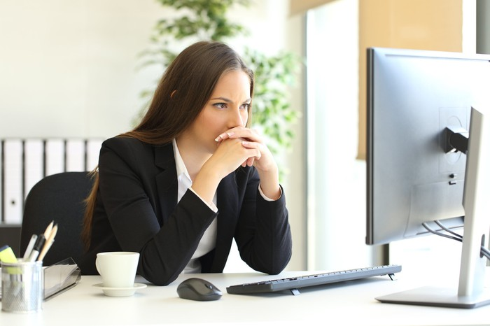 Worried-looking woman in a suit looking at a computer screen.