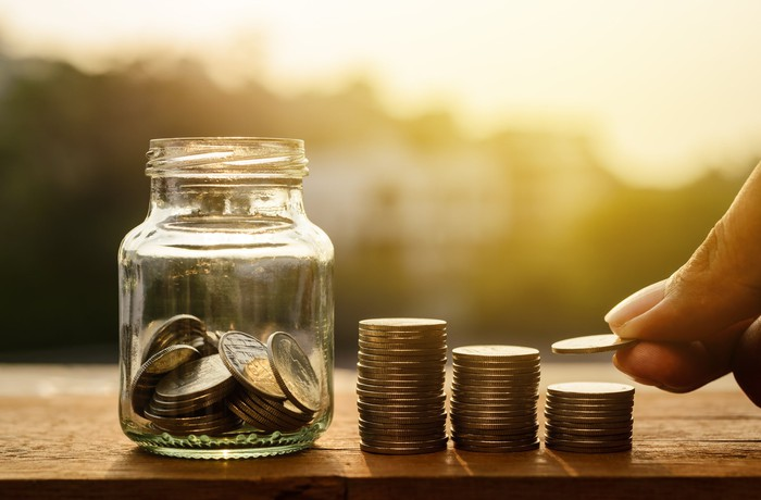 A jar of coins next to rising coin stacks, with a hand holding a coin above one of the stacks.