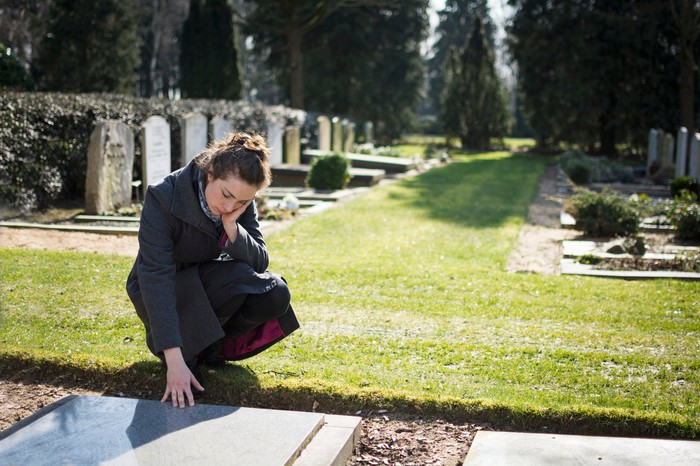 Woman kneeling down and putting her hand on a grave