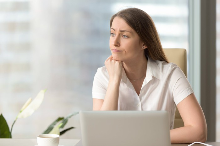 Woman at laptop looking to the side as if distracted
