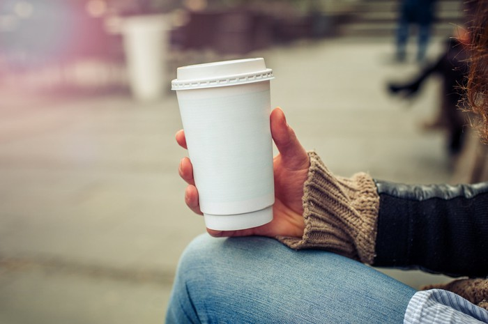 Woman holding a to-go cup