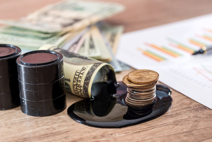 Small oil drums, a pool of black liquid, coins and currency bills, a paper with graphs, and a pen sit on a wooden surface.
