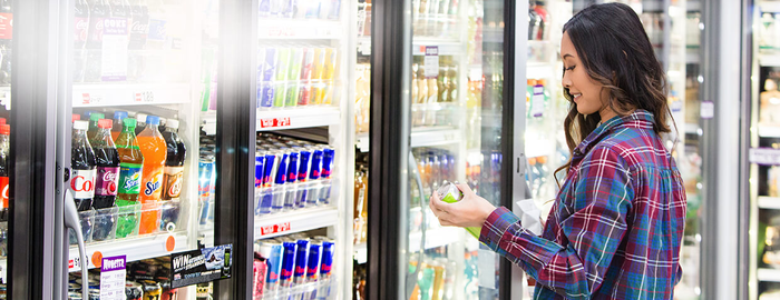 A woman chooses a drink from a refrigerated case in a store.