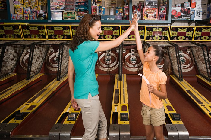 A mother and daughter celebrate while playing an arcade game.