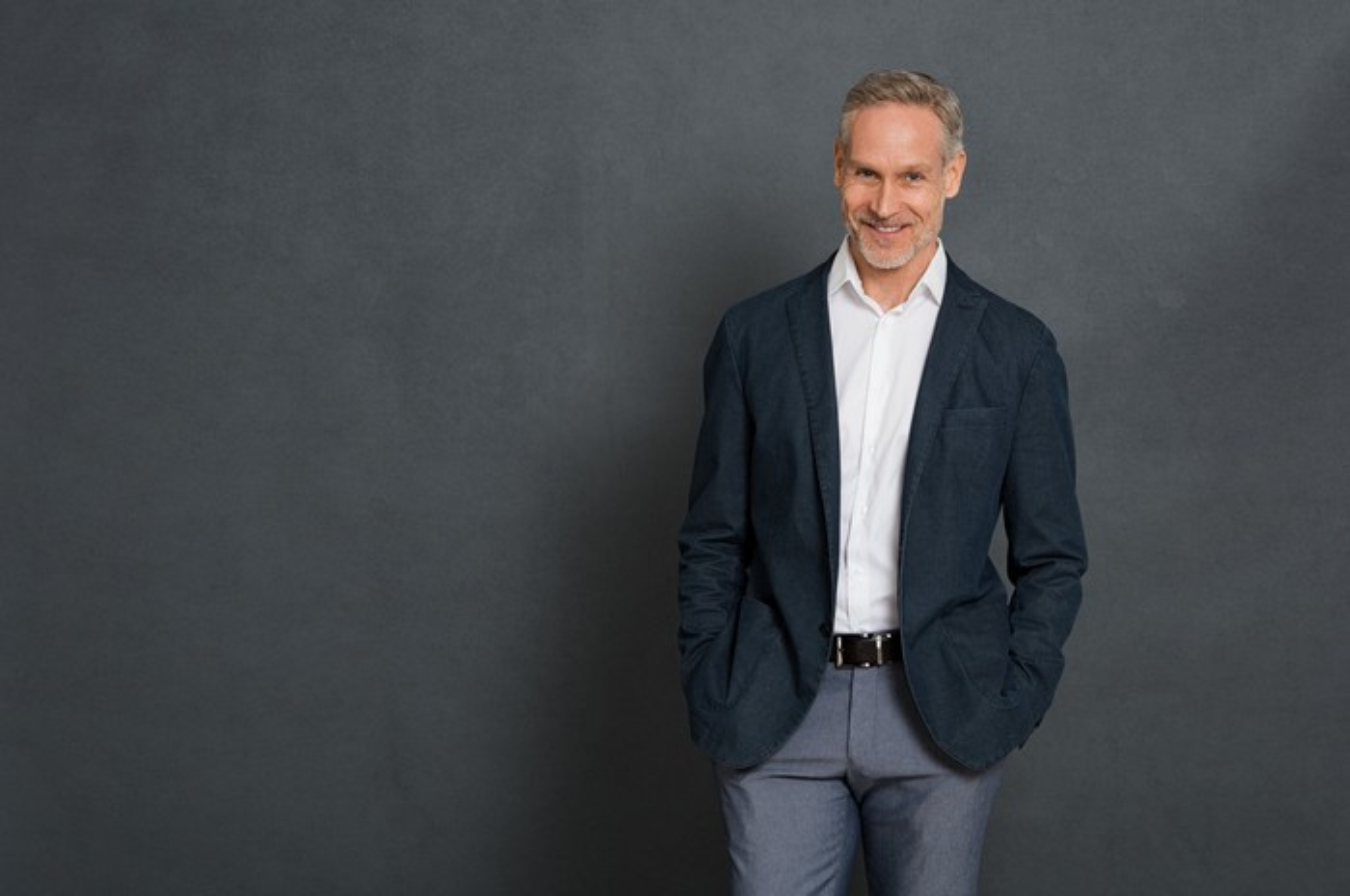 Smiling older man against blackish-gray background