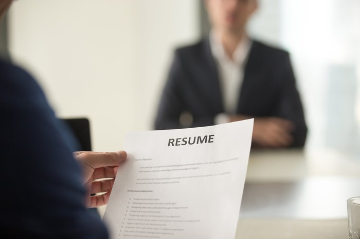Person holding a resume while sitting across from someone in a business suit