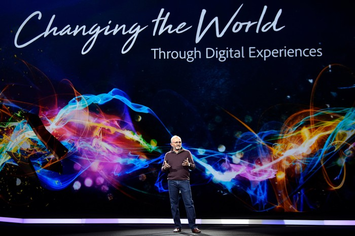 Adobe CEO Shantanu Narayen on a stage in front of a colorful backdrop that reads, Changing the world through digital experiences.