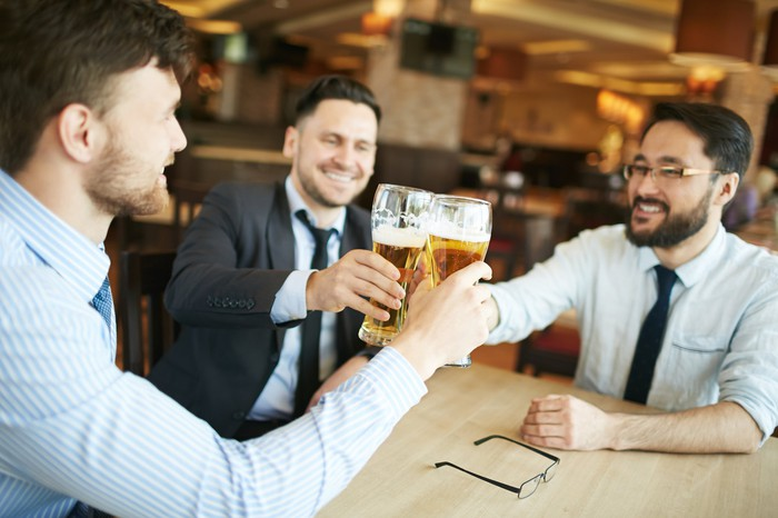 Professionally dressed man clinking beer glasses