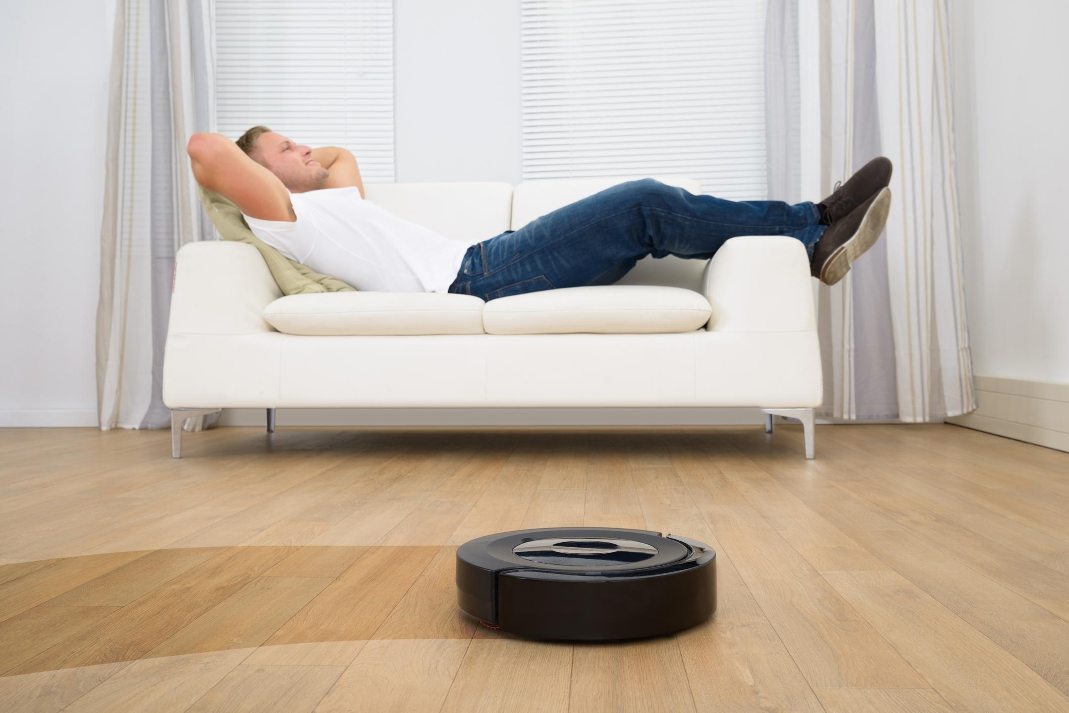 A man reclines as a robotic vacuum cleans his floor.