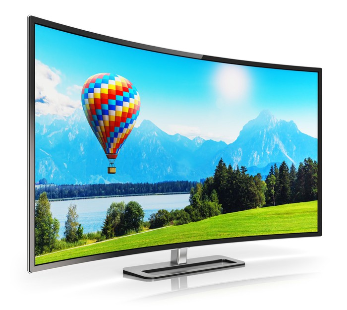 A big-screen TV set with a curved screen, showing a peaceful vista of mountains and a hot-air balloon.