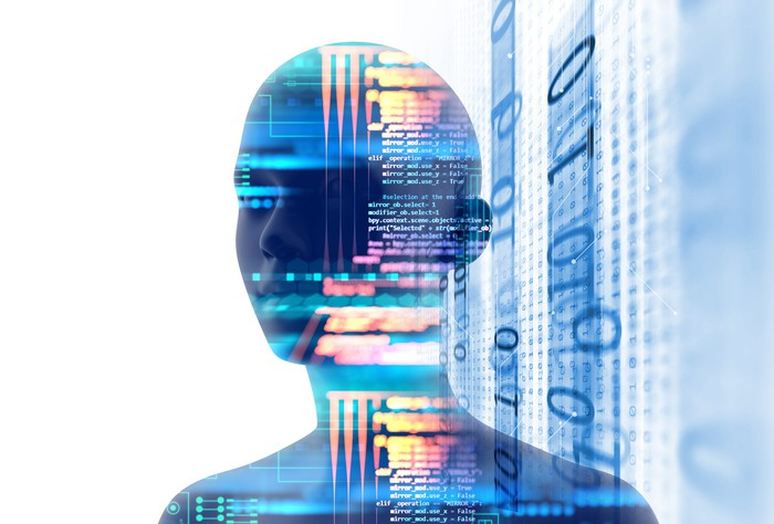 Digital rendering of a human head and shoulders overlaid with computer code, against a background of ones and zeroes