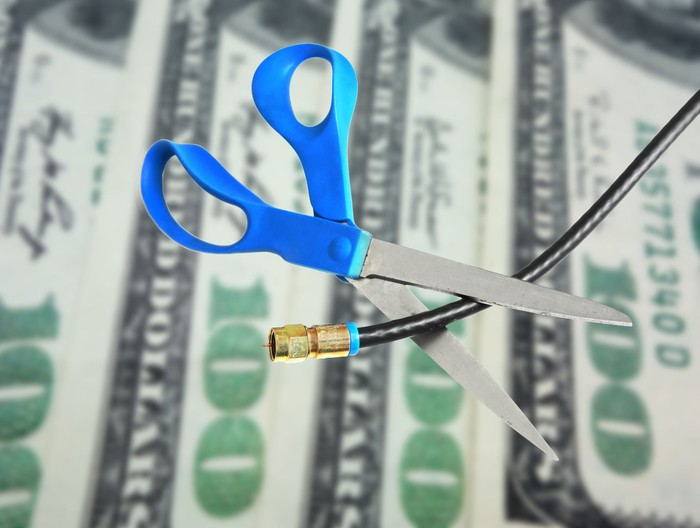 A pair of scissors cuts a cable cord in front of hundred-dollar bills.