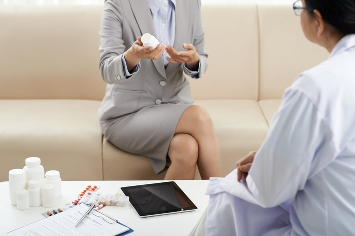 Female pharmaceutical salesperson seated on a couch while presenting products to a doctor.