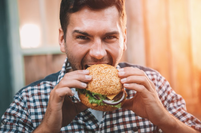 A man takes a bite out of a burger.