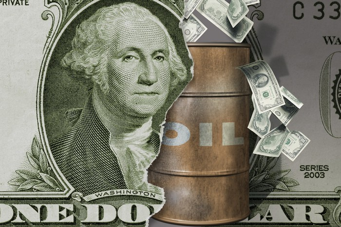 A barrel of oil coming through a dollar bill.