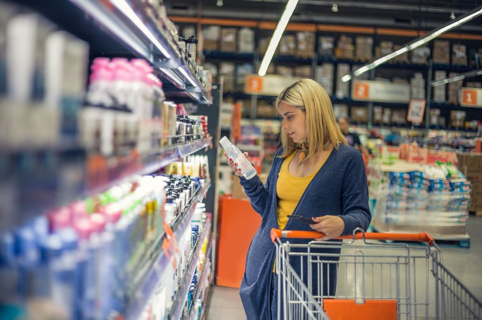 A woman shopping in a supermarket aisle.