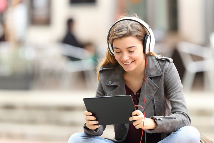 Woman sitting wearing headphones smiling and looking at tablet.