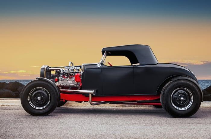black custom hot rod car on a coastal road