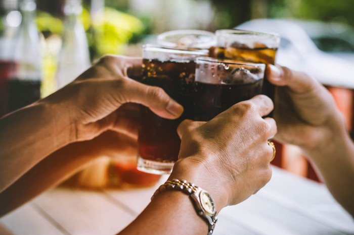 Hands holding glasses of soft drinks next to one another