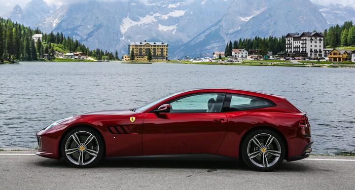 A red Ferrari GTC4Lusso, a low-slung car that looks something like a two-door station wagon.
