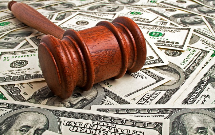 A wooden gavel sitting on $100 bills spread out on a flat surface.