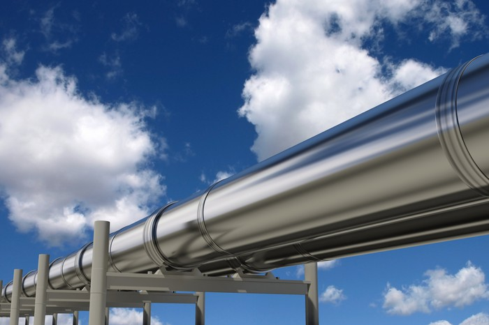 Silver pipelines under a blue sky.