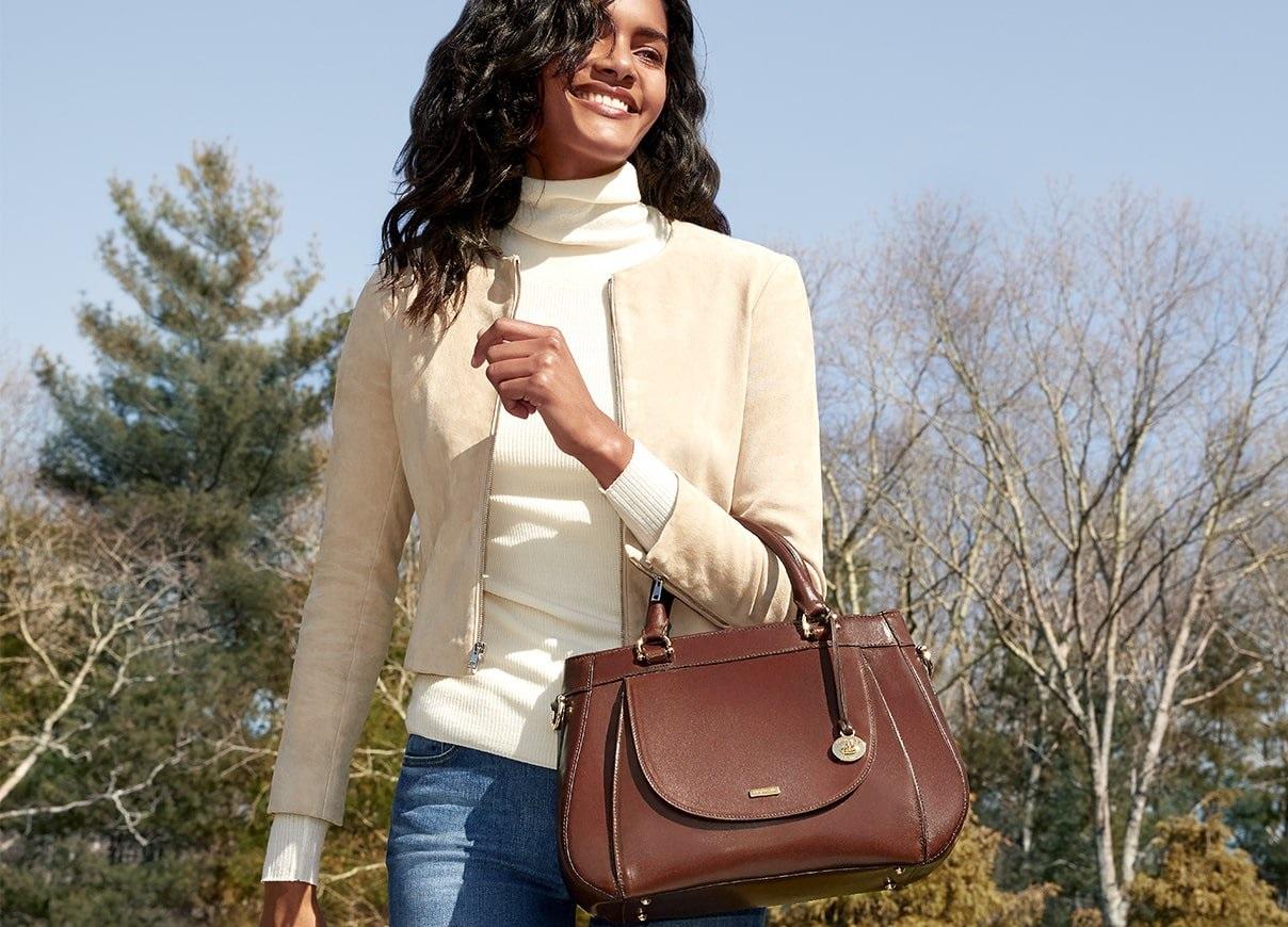 Woman holding a brown leather Brahmin handbag.