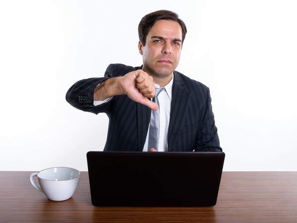 man at laptop giving thumbs down_GettyImages-671663592