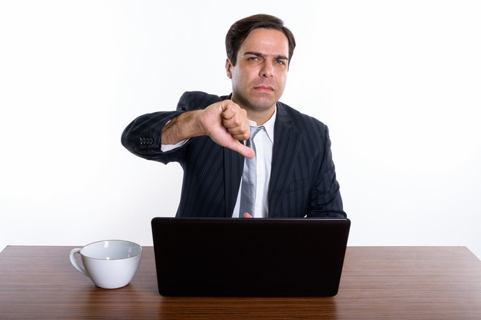 Man at laptop giving thumbs-down sign.